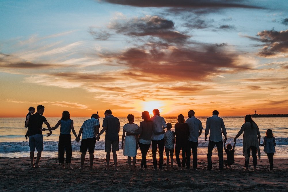 Family standing together on a beach at sunset holding hands