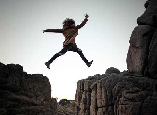 Woman jumping from one rock to another